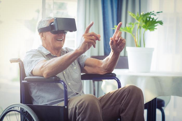 Elderly man using a virtual reality technology headset.