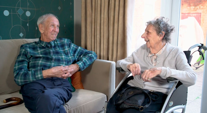 Elderly gentleman and lady smiling at each other in care home setting.