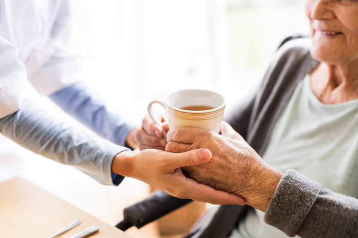 Young healthcare worker handing an elderly lady a cup of tea.