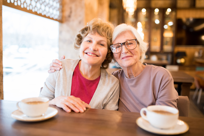 Two lady friends drinking coffee together.