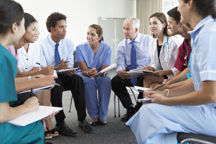 Young healthcare workers sat together discussing industry growth.