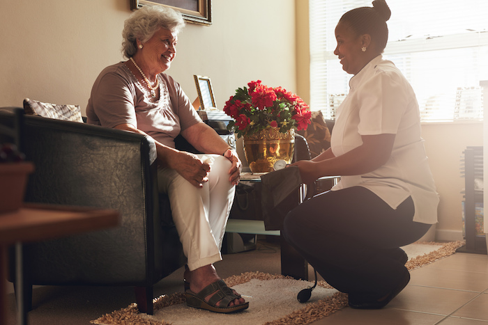 Young healthcare worker with elderly lady, caring for her in her home.
