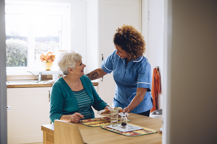 Young healthcare worker comforting an elderly lady in her kitchen.