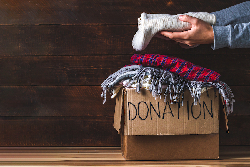 Act of kindness: Piling clothes into a box labelled 'donation'.