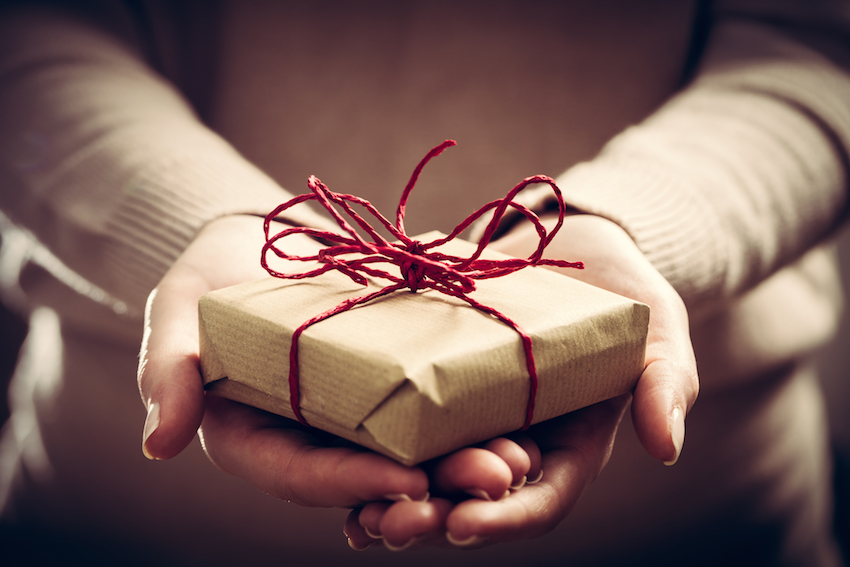 Female hands holding a hand-wrapped gift.