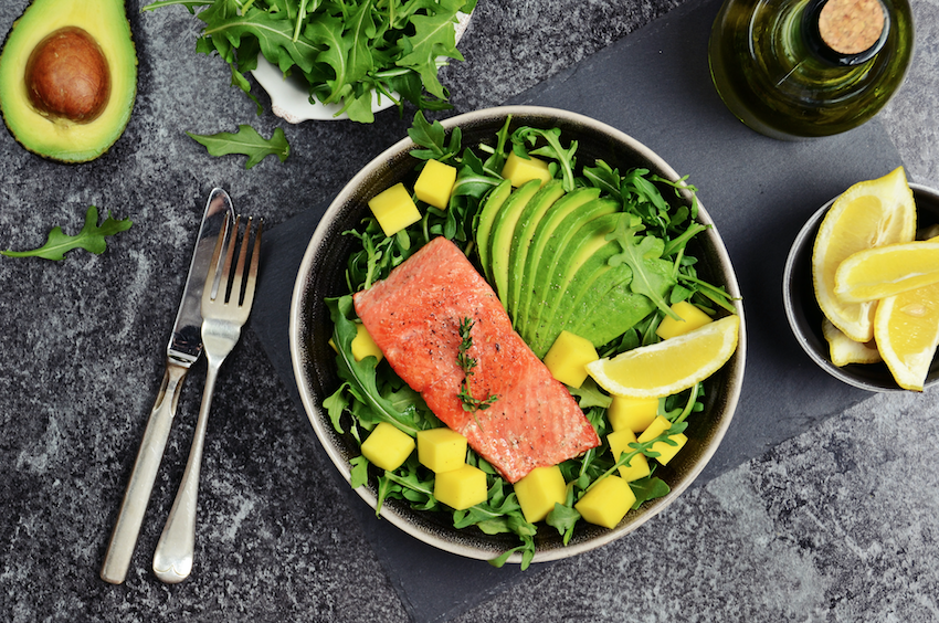 wellbeing in older adults: healthy salmon and salad dish with lemon slices and avocado