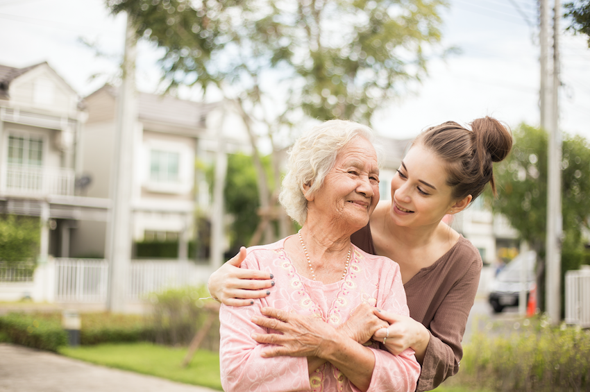 Senior residential care: young carer embracing elderly lady