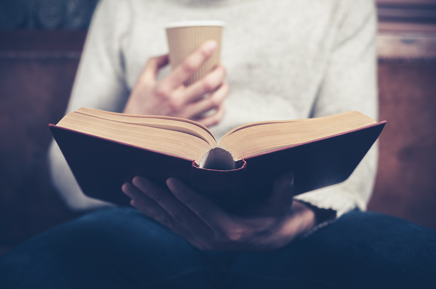 Book club - person holding book with coffee in hand